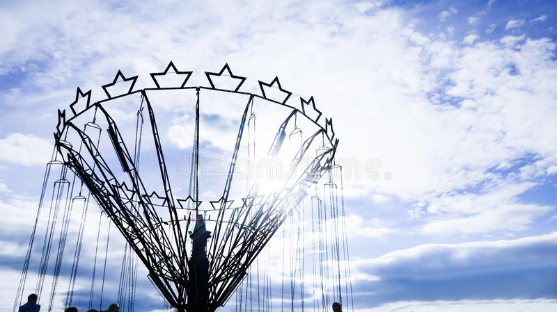 A swinging fair roundabout chain ride. At dusk stock photo