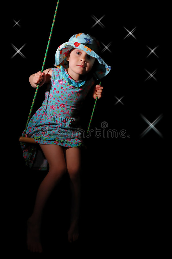 Swinging at night. Little girl swinging on a black background with stars royalty free stock photography