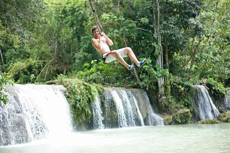 Swinging out terrified at the Cambugahay Falls on Siquijor Island, the Philippines royalty free stock photos