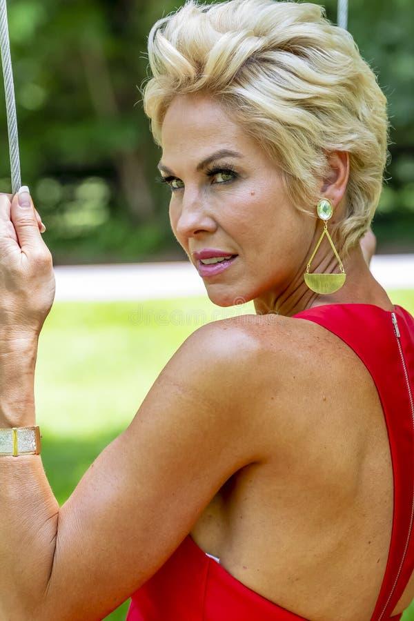 Swinging Outdoors Wearing modèle blond magnifique une robe de soirée rouge images stock