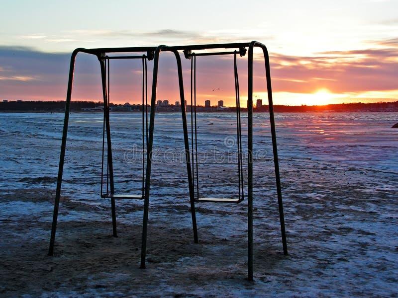 Swings on empty beach royalty free stock photos