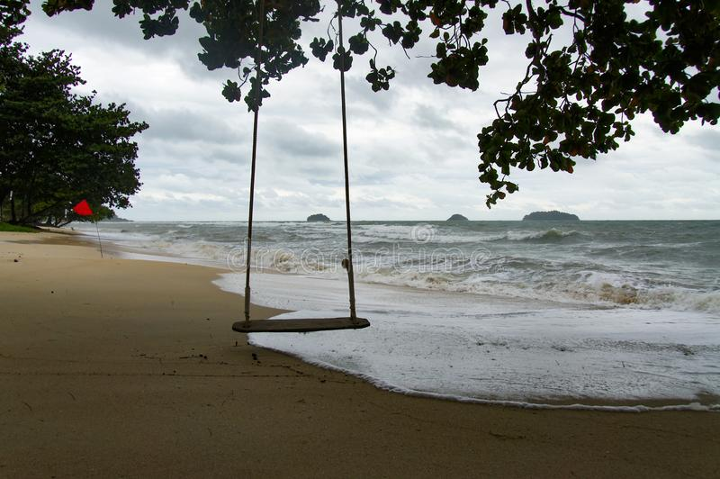 Swings at tree on the sand tropical beach in a rainy day. Koh Chang, Thailand royalty free stock images