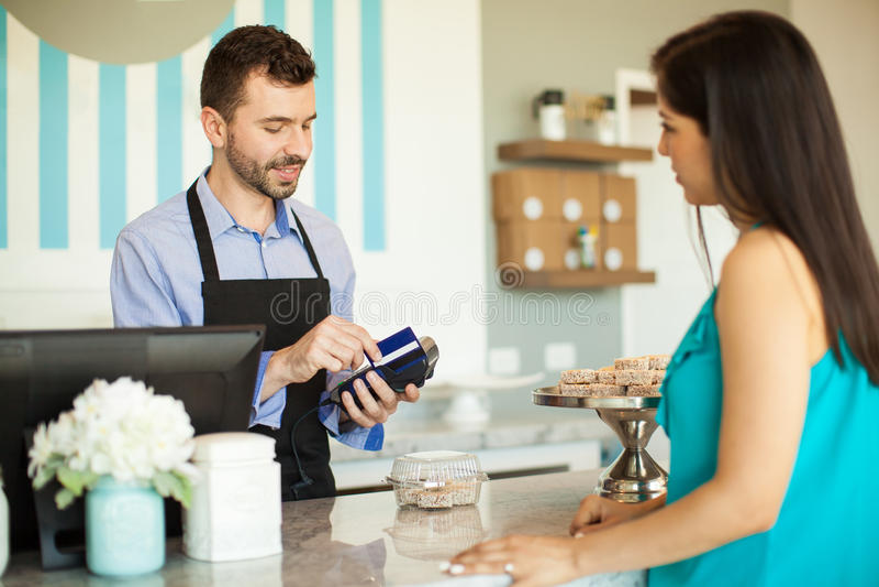 Swiping um cartão de crédito na caixa registadora foto de stock royalty free