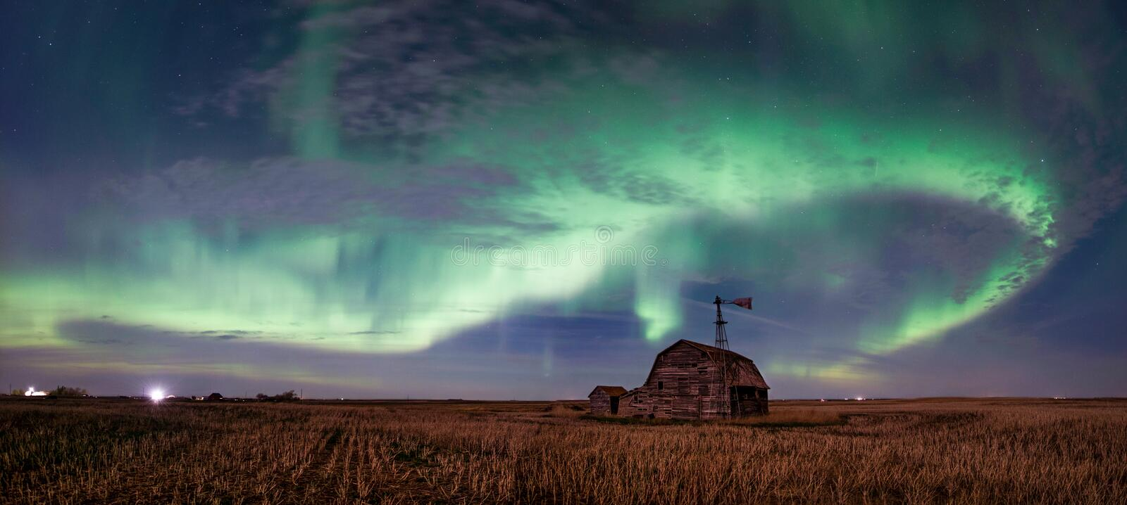 Swirl of bright Northern Lights over vintage barn in Saskatchewan, Canada stock photo