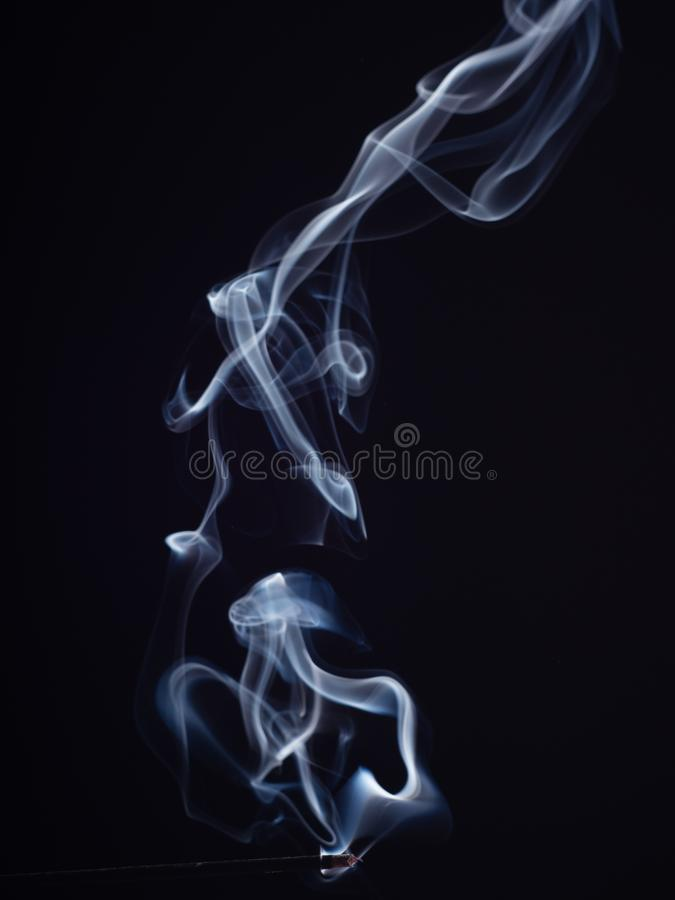 Swirl of white smoke isolated on black background, close up view. Abstract pattern of white smoke, brush effect. Burning. Incense, abstract background. Sweet royalty free stock image