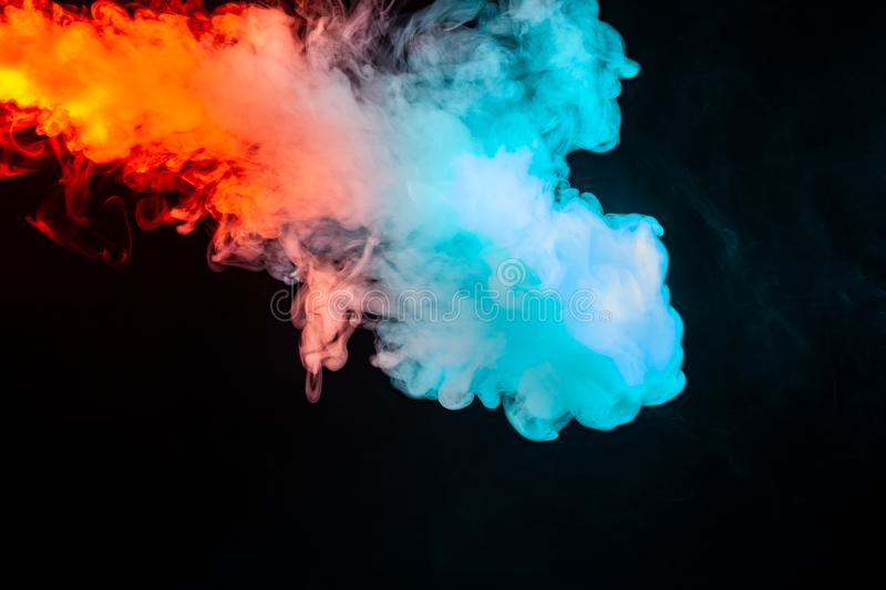 Swirling insulated colored smoke: blue, red, orange, pink; Scrolling on a black background in the dark close up. Concept design. Wallpaper royalty free stock photography