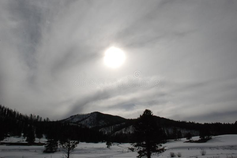 Swirly Winter Clouds with the Sun Trying to Peek Through. A snowy mountain setting with the sun attempting to peek through the swirling clouds, with lots of pine royalty free stock photos