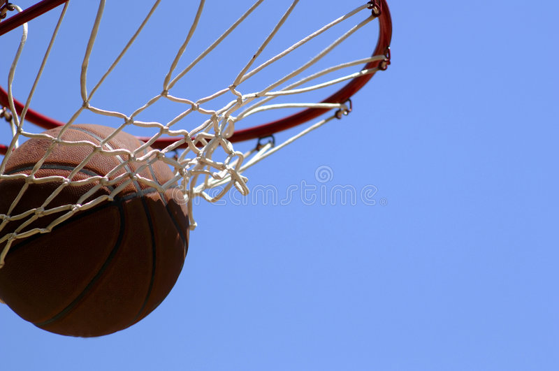 Swish!. Basketball going through net against blue sky stock image