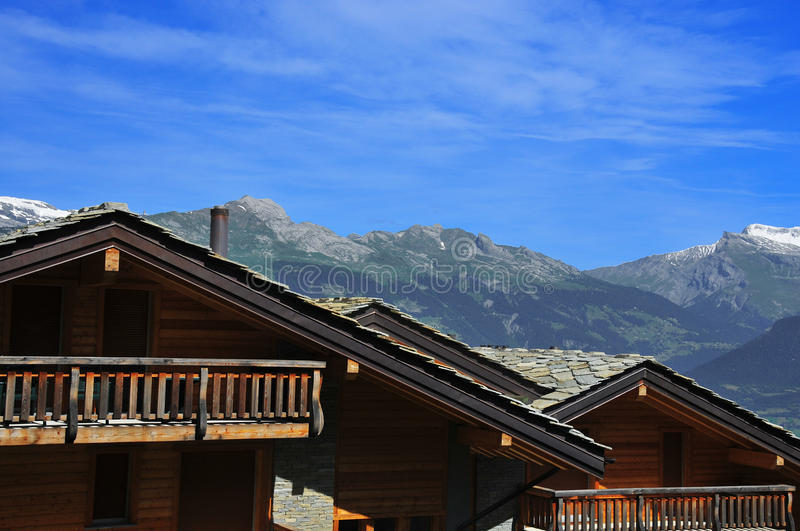 Swiss chalets and mountains. Swiss chalets and snow covered mountains royalty free stock image