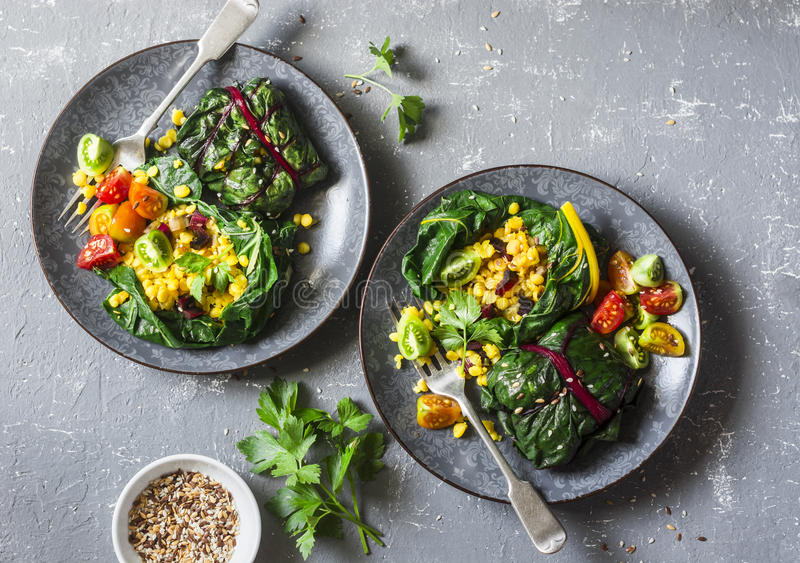 Swiss chard packets. Chard leaves stuffed with turmeric lentils and vegetables. Vegetarian healthy food concept. On a grey backgro royalty free stock photo