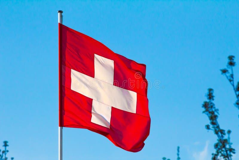 Swiss Confederation, Switzerland national flag. Waving on blue sky background stock images