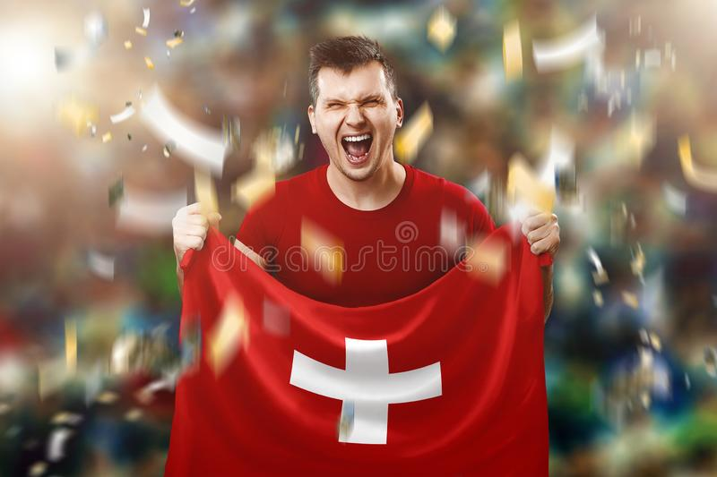 A Swiss fan, a fan of a man holding the national flag of Switzerland in his hands. Soccer fan in the stadium. Mixed media. A Swiss fan, a fan of a man holding royalty free stock image