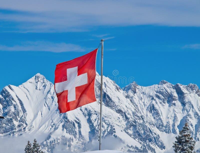 Swiss flag. Against snowy mountains stock photos