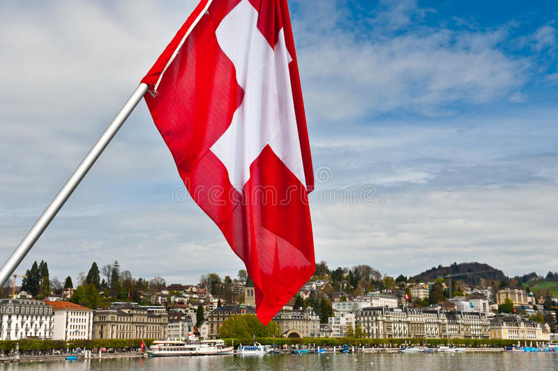 Swiss Flag. On the Background of the Embankment of the River Reuss in Lucerne royalty free stock images