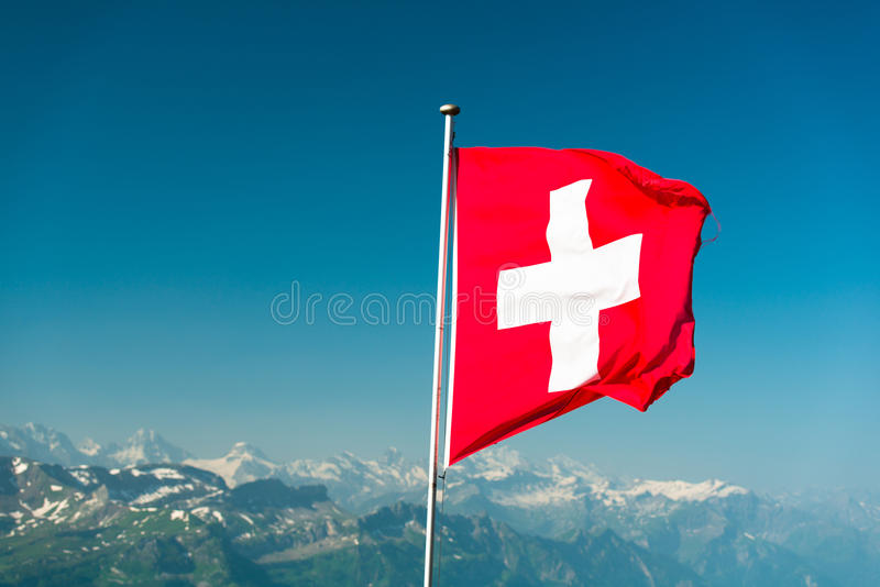Swiss flag. With blured mountains in the background. View from Brienzer Rothorn, Switzerland royalty free stock photography