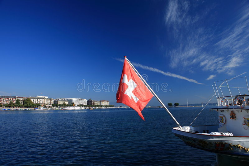 Swiss Flag. From a ship, blue sky and white cloud, and the lake senery demonstrate a typical Geneva picture stock image