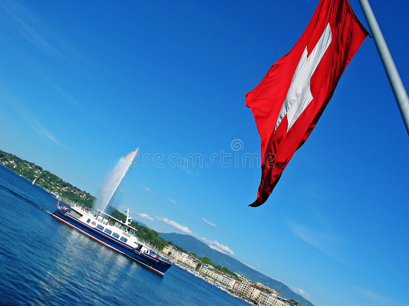 Swiss flag. Geneva's Lake. View to the swiss flag, fountain and small boat stock image