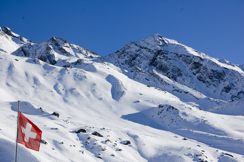 Swiss Flag. Against a snow covered mountain in the Swiss Alps royalty free stock photo
