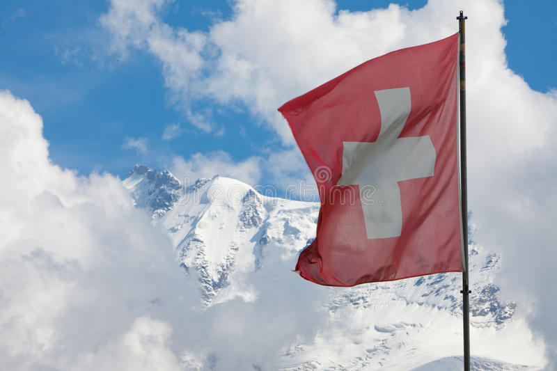 Swiss flag in the Alps. Swiss flag fluttering before a beautiful alpine snow covered mountain backdrop royalty free stock images