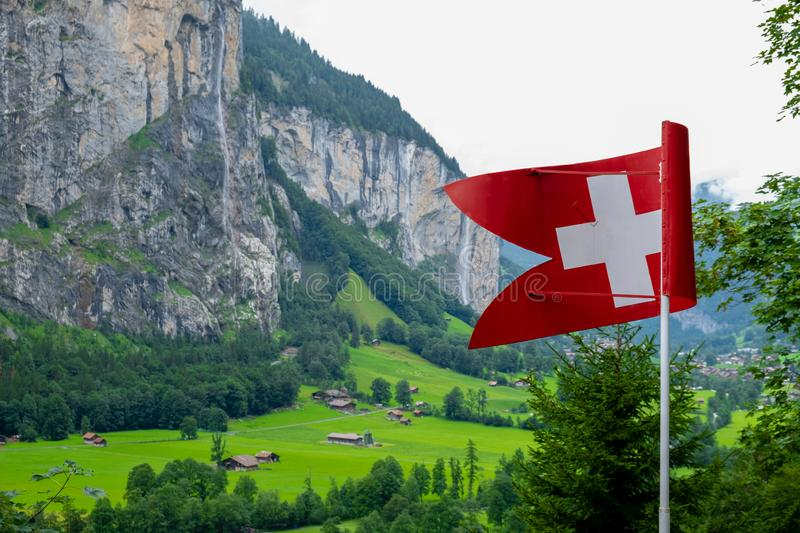 Swiss flag. And in the background its typical mountains royalty free stock image
