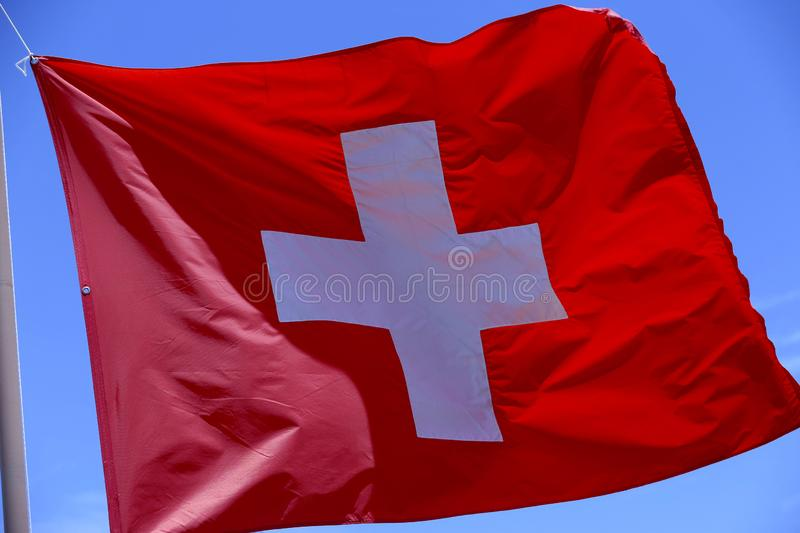 Swiss flag. Blowing in the wind with blue sky on background royalty free stock photography