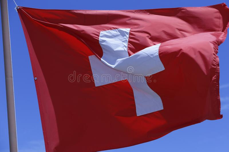 Swiss flag. Blowing in the wind with blue sky on background stock images