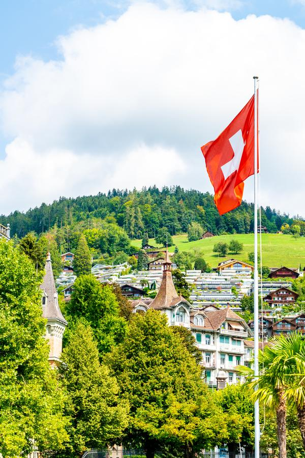 Swiss flag with blue sky. And city royalty free stock photos