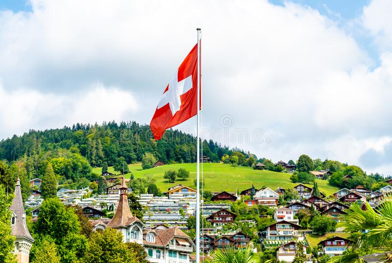 Swiss flag with blue sky. And city stock photo