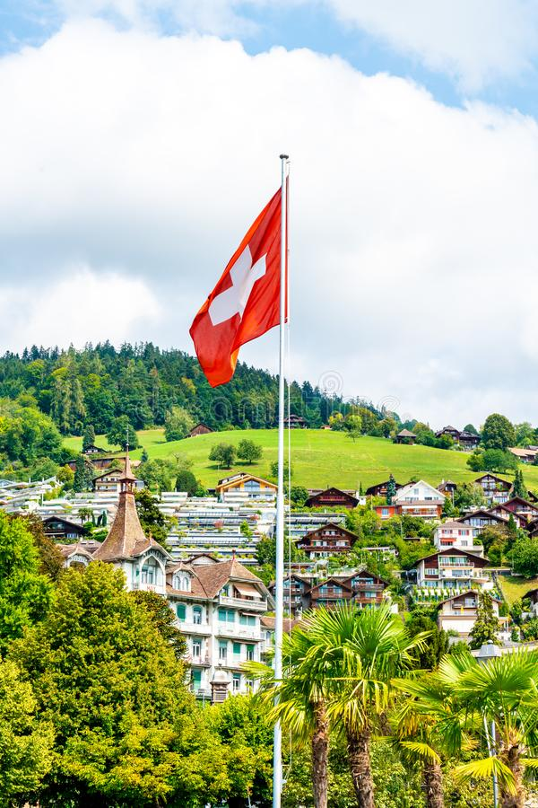 Swiss flag with blue sky. And city stock image
