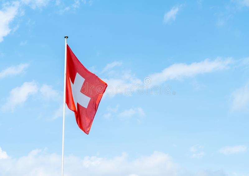 Swiss flag with sky. Swiss flag with blue sky stock image