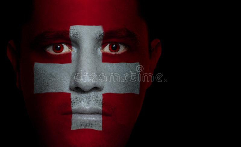 Swiss Flag - Male Face. Swiss flag painted/projected onto a man's face royalty free stock photography