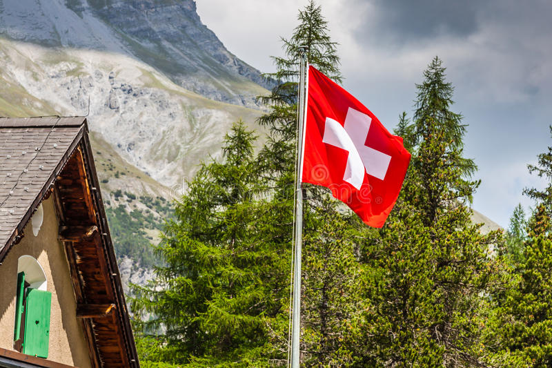 Swiss flag - national symbol of Switzerland with Alps in background royalty free stock photography