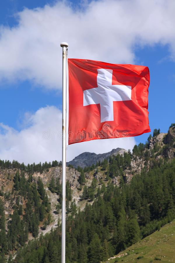 Swiss flag. National symbol of Switzerland with Alps in background. Graubunden canton (Grisons royalty free stock photography