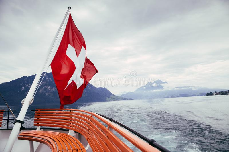 Swiss flag over landscape of lake and cloudy mountain in Switzerland royalty free stock photography