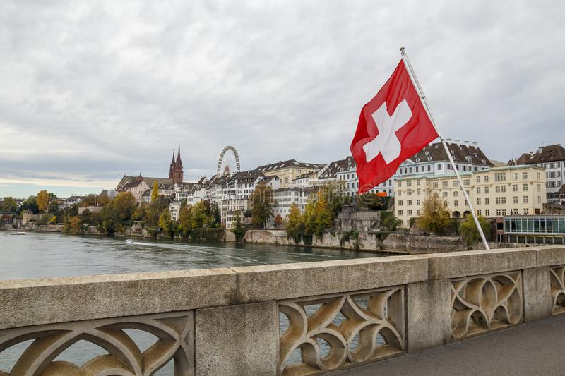 Swiss flag over the river Rhine in Basel, Switzerland. Swiss flag over the river Rhine in Basel, with the Munster and ferris wheel in the background stock photography