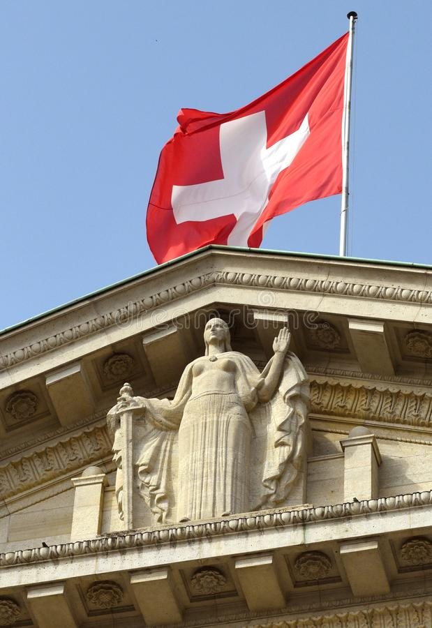 Swiss flag and statue of Justice on Federal Supreme Court of Switzerland. Lausanne, Switzerland royalty free stock photos
