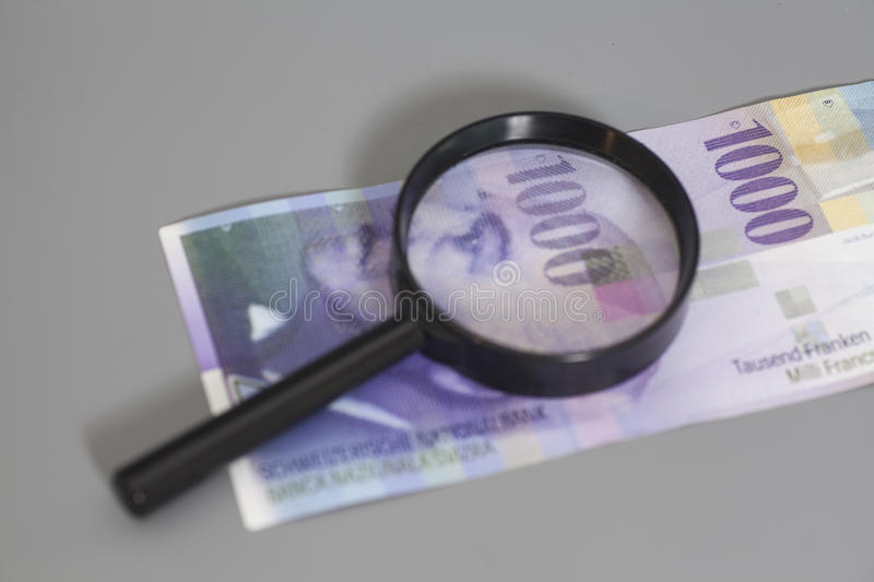 Swiss 1000 Franc banknotes under magnifying glass stock image