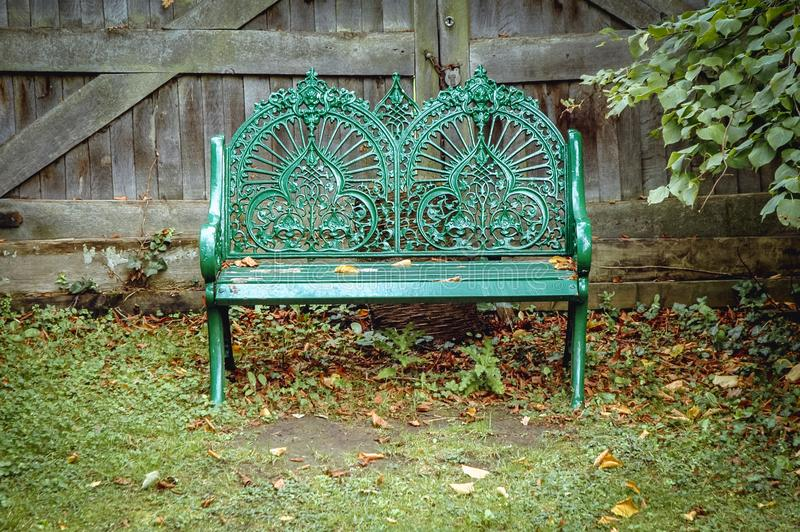 Swiss Garden in Biggleswade. Green metal bench in Swiss Garden in Old Warden Park located in Biggleswade on the River Ivel in Bedfordshire, UK royalty free stock photos