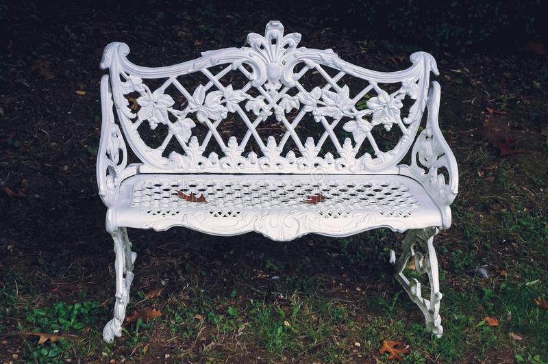Swiss Garden in Biggleswade. White metal bench in Swiss Garden in Old Warden Park located in Biggleswade on the River Ivel in Bedfordshire, UK royalty free stock photos