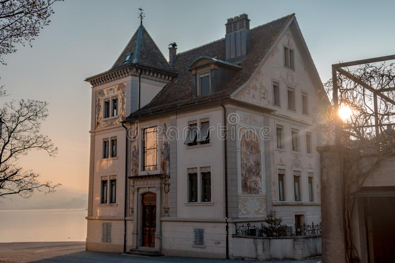 Swiss historic house by a lake. At sunset stock photography