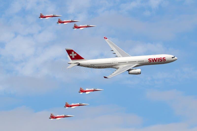 Swiss International Air Lines Aerobus A330 samolotu latanie w formacji z Northrop F-5 samolotem Patrouille Suisse pokazu herbata fotografia stock