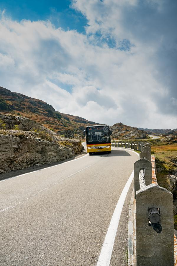 Swiss post bus on a two-lane road leading over a high remote and wild mountain pass in the Swiss Alps royalty free stock photo