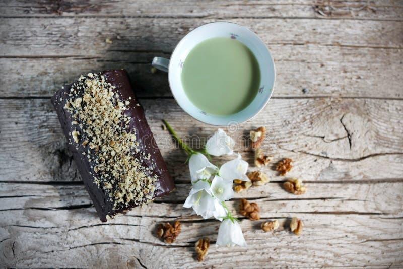Swiss roll del cioccolato con le noci e la tazza di tè verde fotografia stock libera da diritti