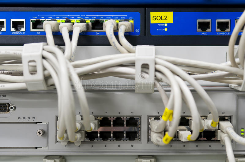 Switch, firewall and router IT equipment. IT environment with switch and firewalls connected with grey patch ethernet cables stock photo