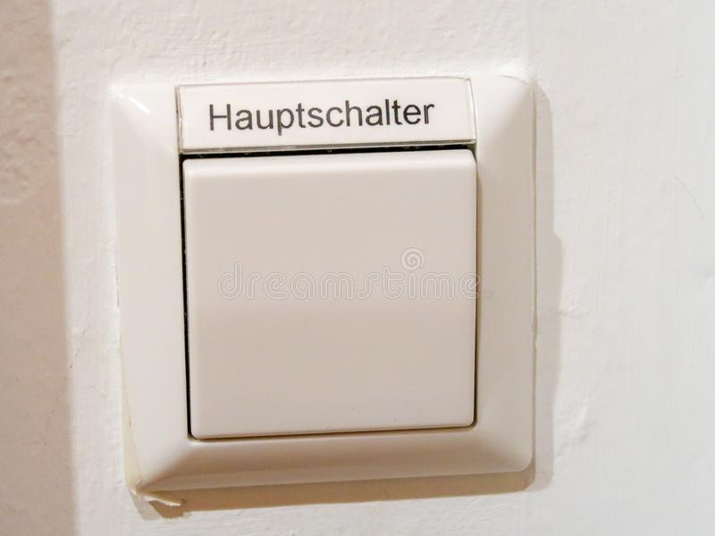 A switch with the german inscription for main switch. A white button switch with the german inscription for `main switch stock image