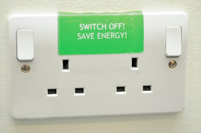 Save energy sign on plug sockets. Green switch off and save energy sign on twin electric plug sockets royalty free stock photos