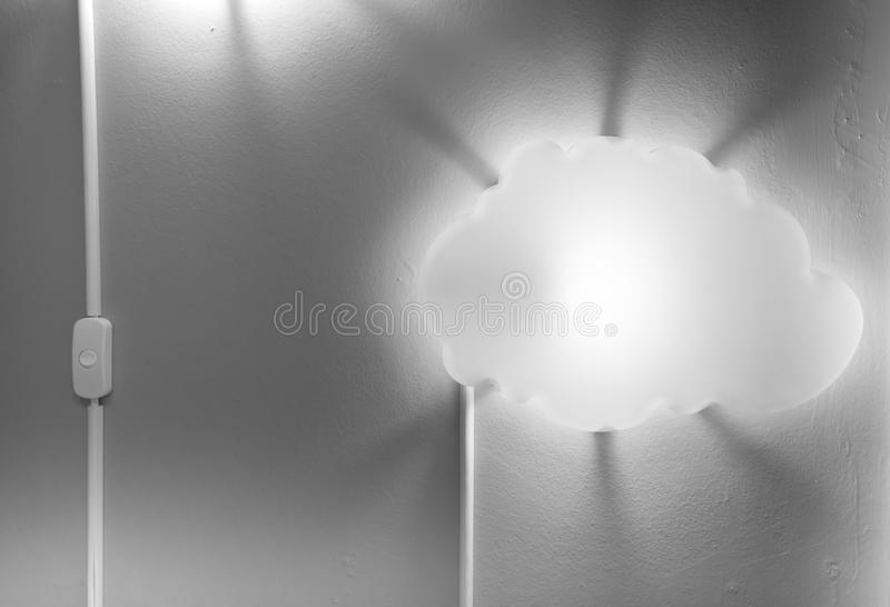 Switch turned on next to illuminated white cloud-shaped lamp attached on grey wall with scattered dark shadow royalty free stock photos