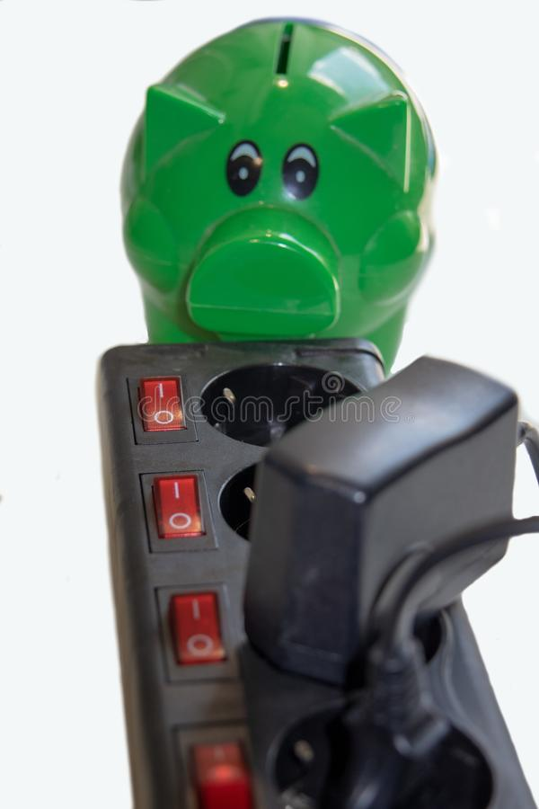 Save money with energy savings. Switchable socket power strip with green piggy bank with money.Save money with energy savings royalty free stock photography