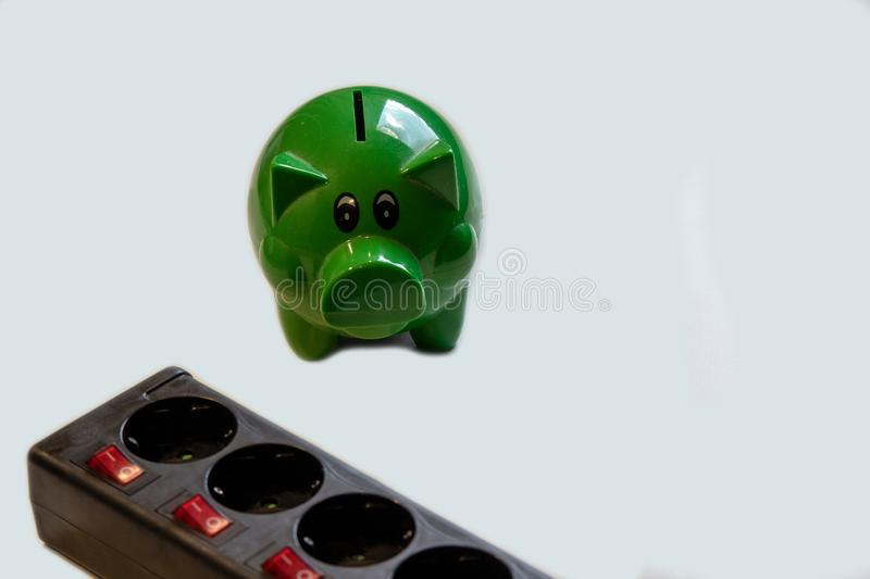Save money with energy savings. Switchable socket power strip with green piggy bank with money.Save money with energy savings stock image