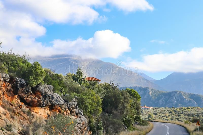 Switchback in paved two lane highway through the Taygetus mountain range on the Peloponnese in Greece with tile roofed houses royalty free stock photography